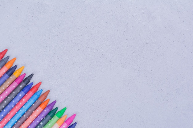 灰色のカラフルなクレヨンや鉛筆。