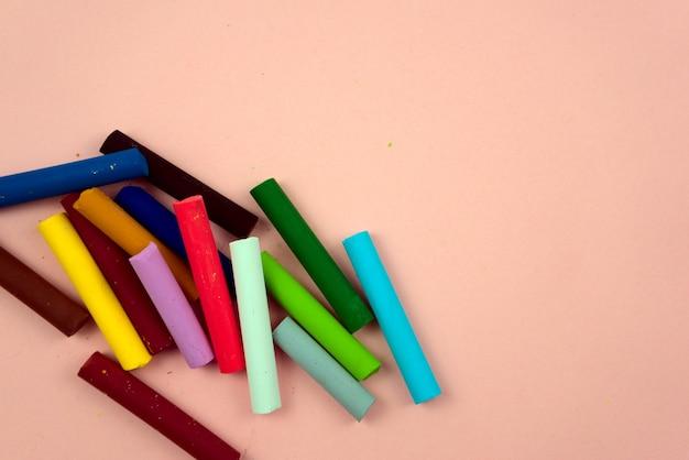 Разноцветные мелки пастельные разнообразные цветные мелки с плоским лежат на розовом пастельном фоне