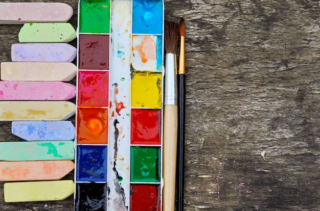 Colorful crayons and watercolor on wooden background