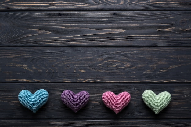 Colorful crocheted hearts on rustic gray wooden table.