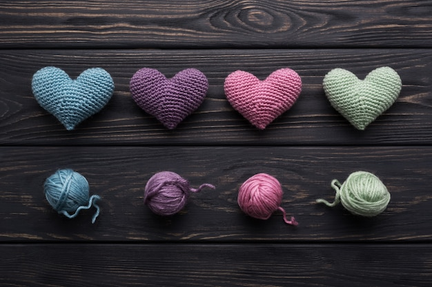 Colorful crocheted hearts and skeins on gray wood table