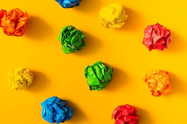 在黄色背景的五颜六色的被弄皱的纸球
