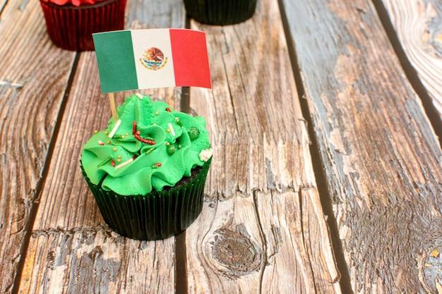나무 판자에 멕시코 국기로 장식된 다채로운 컵케이크