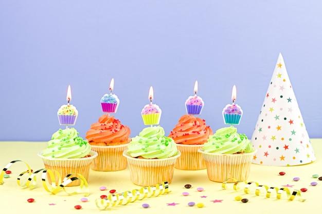 불타는 초, 파티 모자, 깃발, 색종이와 화려한 컵 케이크
