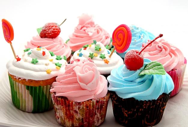 ピンクの霜付けとふりかけのカラフルなカップケーキ