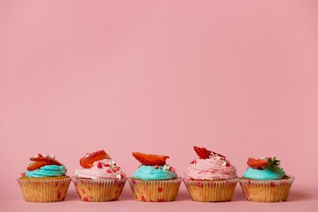 Разноцветные кексы с посыпкой и ягодами сверху