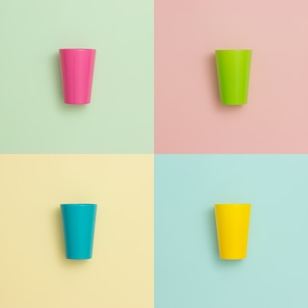Colorful cups on different pastel backgrounds.