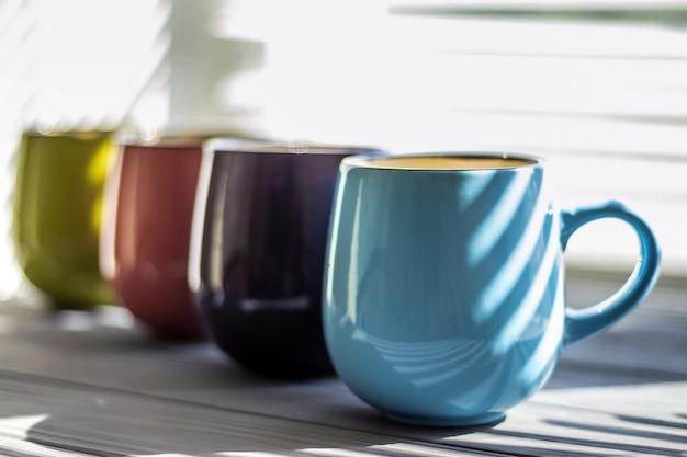 テーブルのクローズアップのカラフルなカップ