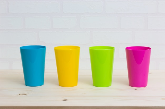 Colorful cups on wooden table white brick wall.