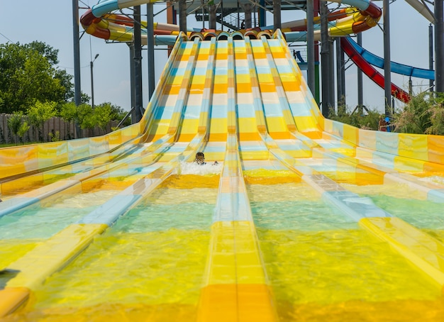 Colorful curved water slide at an amusement park or tropical resort curving towards the camera with a small boy half way down