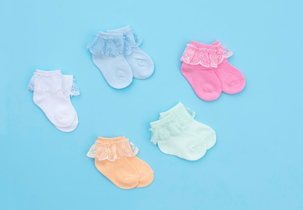 Colorful cute baby socks on blue background. baby accessories. flat lay.
