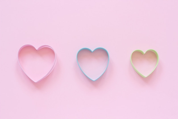 Colorful cutters cookies in heart shape on pastel pink background. concept valentine's card.