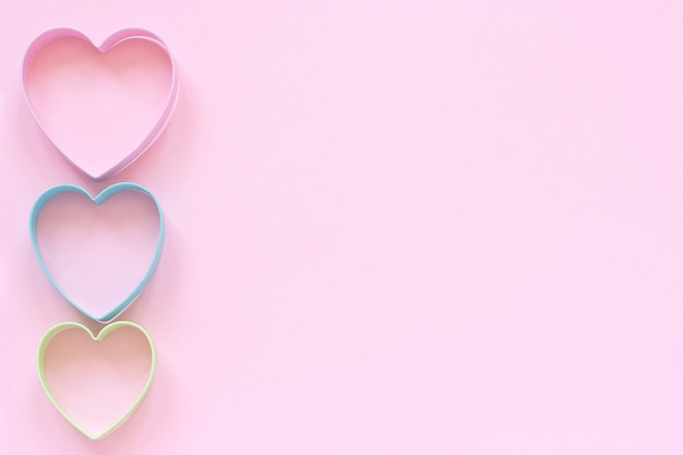 Colorful cutters cookies in heart shape on pastel pink background