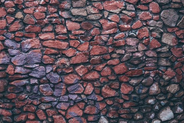 Красочная темная мокрая текстура каменной стены из окрашенного гранита неравномерно