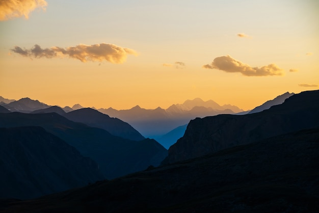 Colorful dawn landscape with beautiful blue mountains silhouettes and golden gradient sky with clouds.