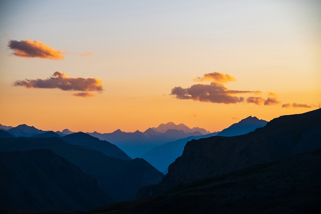 Colorful dawn landscape with beautiful mountains silhouettes and golden gradient sky with lilac clouds.