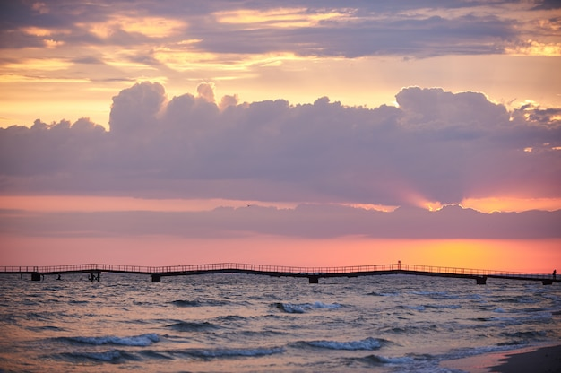 Colorful dawn over the sea. pier on the horizon.