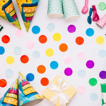 Colorful decorated confetti with party hats; gift box; balloons and wrapped gift box on white background
