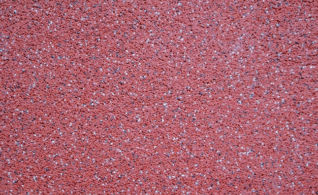 Colorful decorative mosaic plaster in burgundy or red. wall texture, background. granular, structured, rough, uneven textured coating. modern exterior cladding.