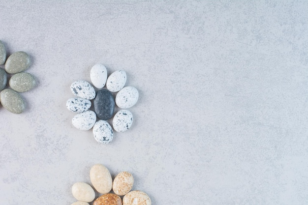 Pietre decorative colorate per la lavorazione su sfondo di cemento.