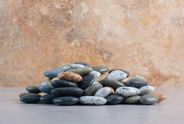 Разноцветные декоративные камни для крафта на бетонном фоне.