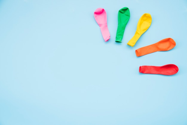 Colorful deflated balloons on blue background