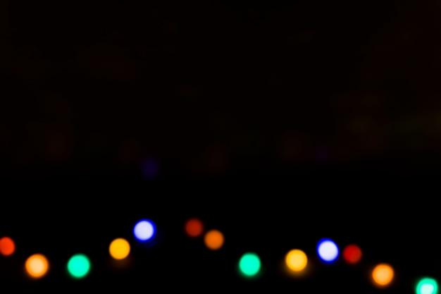 Colorful defocused light bulbs on black backdrop