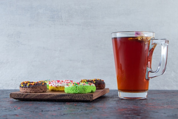 Colorful delicious donuts on wooden board with glass of tea.