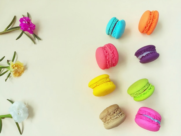 Colorful delicious macaroons and sweet flowers are placed on yellow background