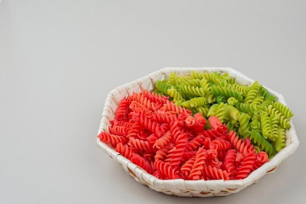 Красочные вкусные сырые макароны на тарелке