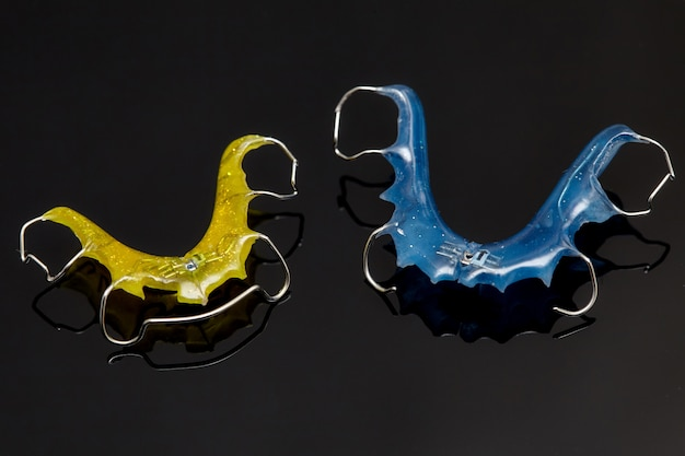 Colorful dental braces or retainers for teeth on glass wall