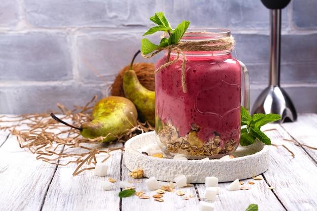 붉은 열매, 배, 그 라 놀라 및 마른 코코넛 큐브와 화려한 해독 여름 스무디