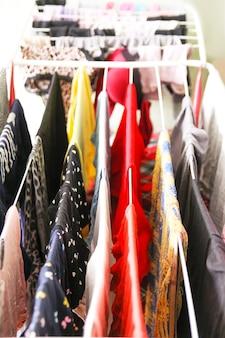 Красочное различное платье и белье, висящее на сушилке.
