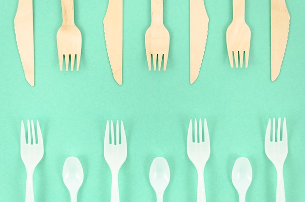 Colorful disposable cutlery on turquoise background