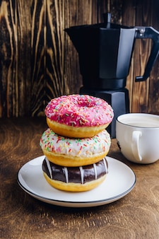 Colorful donuts breakfast composition with different color styles of doughnuts and fresh coffee