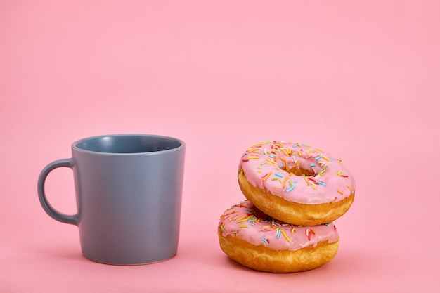 さまざまな色のスタイルでカラフルなドーナツの朝食の構成。色のゲーム、甘い生活。コピースペース、ピンクの背景。
