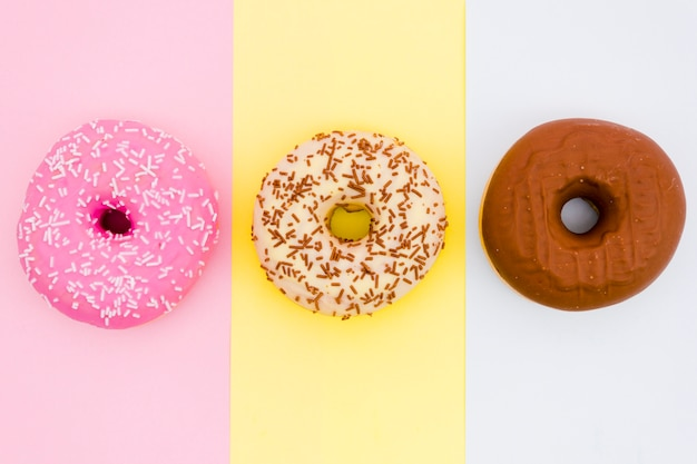 Colorful donuts on colored striped backdrop