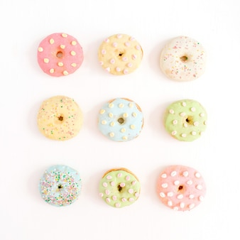 Красочные пончики на белом фоне. плоская планировка, вид сверху