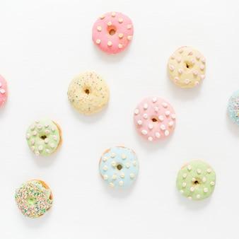 Красочные пончики на белом. плоская планировка, вид сверху минимальный узор.