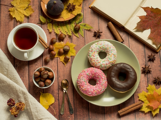 Colorful donuts on plate autumn and a cup of tea on rustic wooden surface