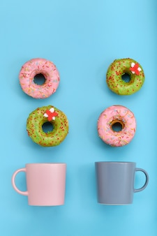 Красочные пончики с глазурью и чашки кофе на пастельно-голубой поверхности