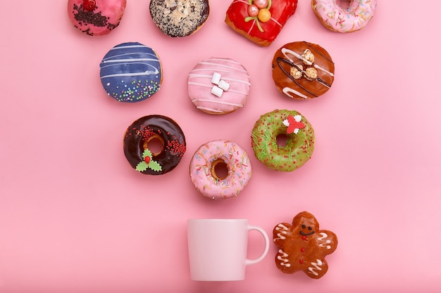 파스텔 장미 표면에 장식 및 커피 컵과 다채로운 도넛