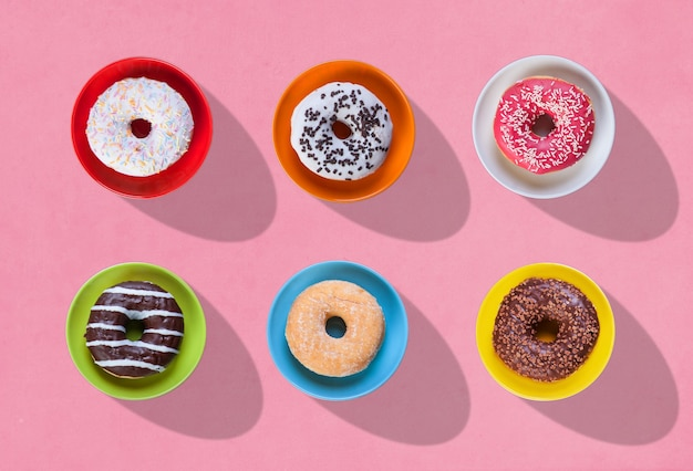 Colorful donuts with shadows and different flavors on plates on a pink background. view from above