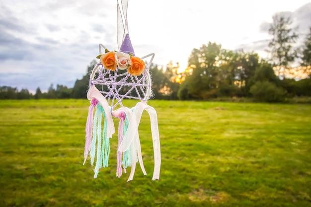 여름 자연 배경 야외에서 다채로운 드림 캐쳐입니다. 깃털, 리본, 실, 구슬로 만든 수제 장식.
