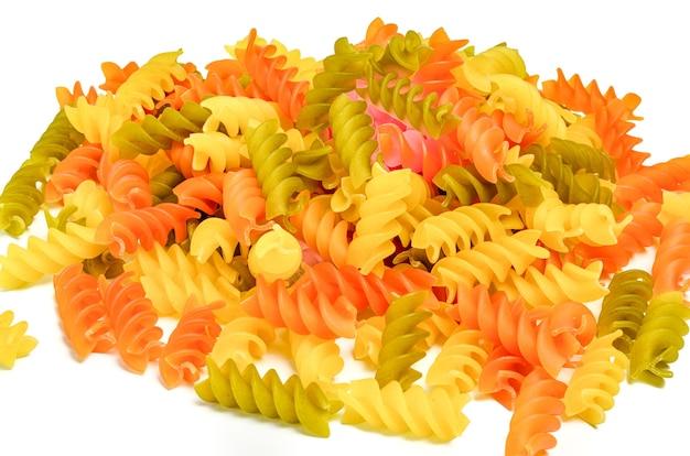 Красочные сушеные три цветные макаронные изделия фузилли, изолированные на белом.