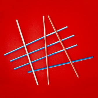 Colorful drinking straws on red background