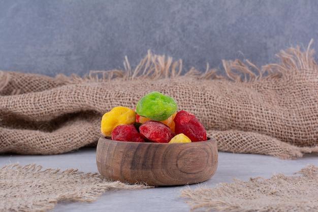 木製のカップにカラフルなドライフルーツ。高品質の写真