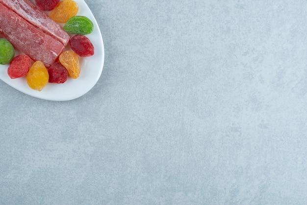 Красочные ягоды сухого мармелада в белой тарелке. фото высокого качества