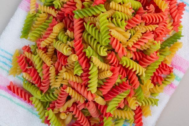 Pasta colorata a spirale secca sulla tovaglia