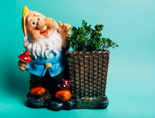 Colorful dwarf figure with plants against turquoise background